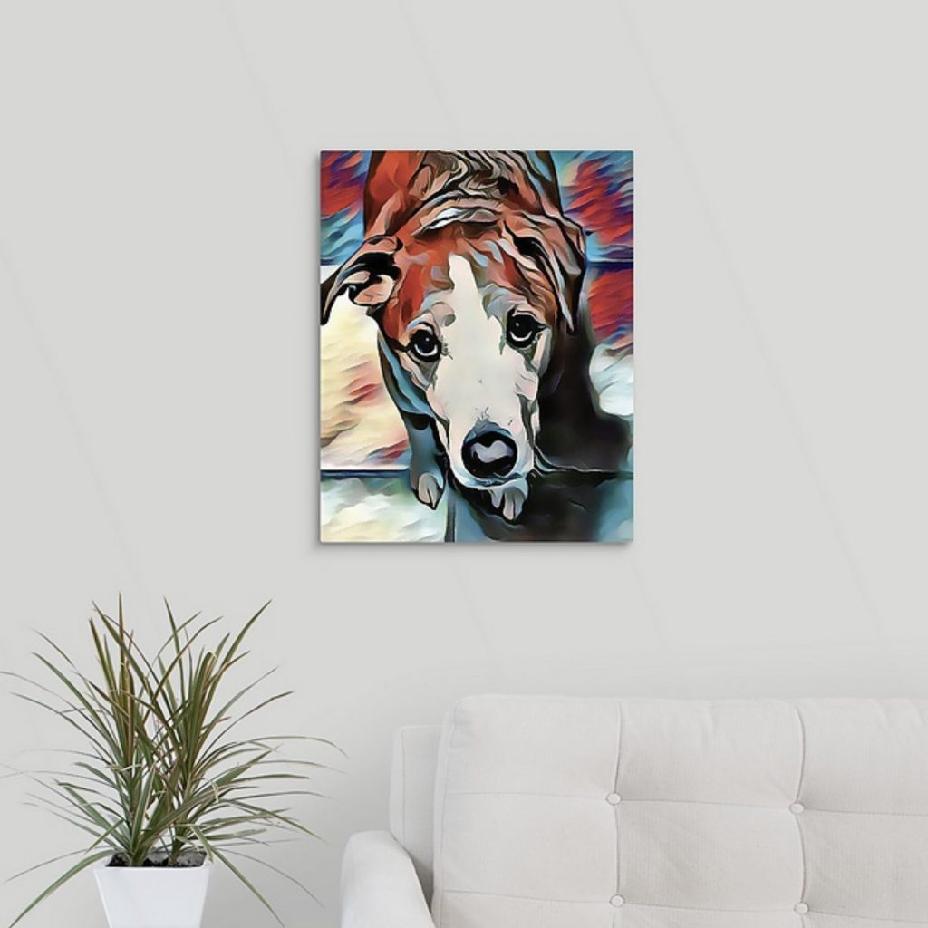 White couch and plant with a wall hanging of a Stylized Image of a dog in blues and reds looking up at the viewer.