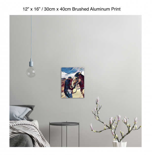 12 inch by 16 inch brushed aluminum print of a woman kissing a horse on the nose in front of a desert background hung on the wall above a metal table next to a bed
