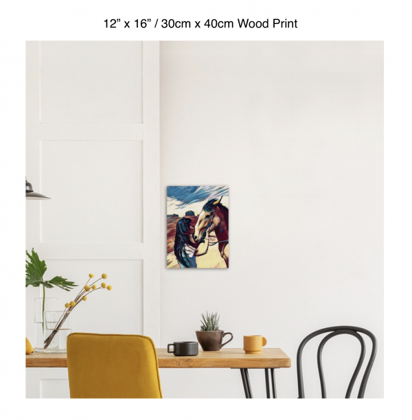 12 inch by 16 inch wood print of a woman kissing the nose of a horse hung above a kitchen table