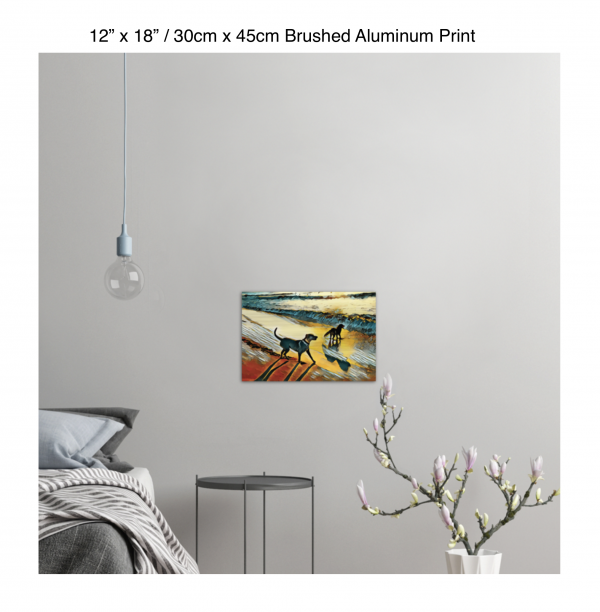 18 inch by 12 inch brushed aluminum print of two dogs wading in the surf in golden tones of a sunset hung on the wall above a metal table next to a bed