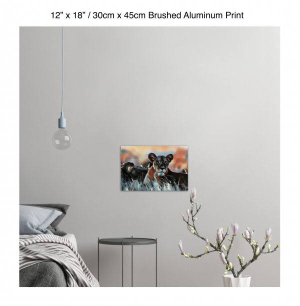 18 inch by 12 inch brushed aluminum print of a lioness hanging in a bedroom over a night table next to a small table with a plant