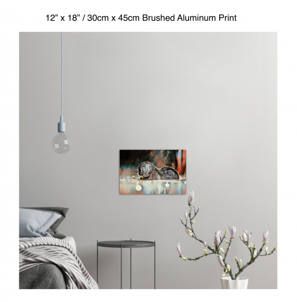 18 inch by 12 inch brushed aluminum print of an otter hanging in a bedroom over a night table next to a small table with a plant
