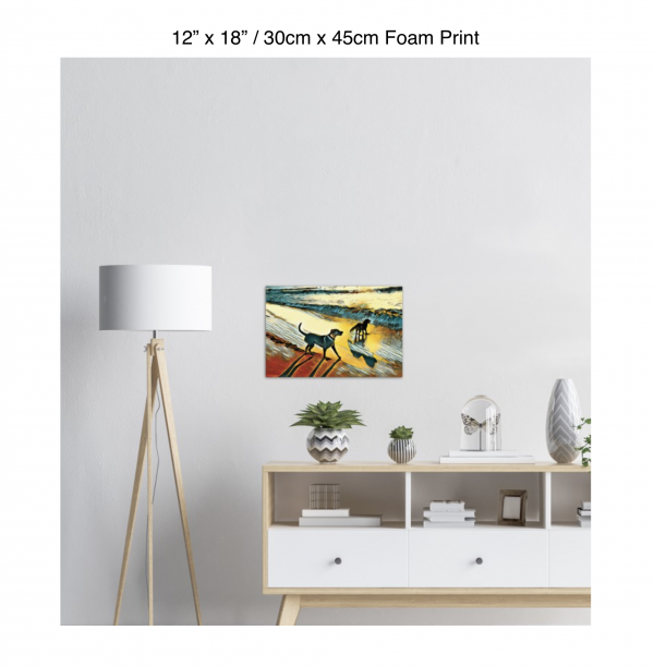 18 inch by 12 inch foam print of two dogs wading in the surf in golden tones of a sunset hanging over a credenza next to a floor lamp