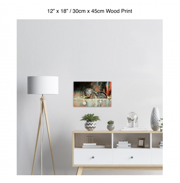 18 inch by 12 inch wood print of an otter hanging over a white credenza next to a white floor lamp