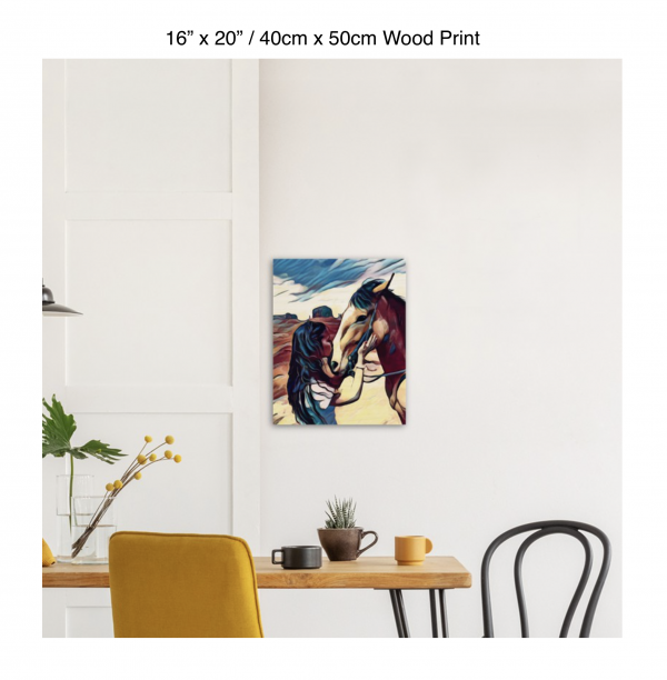 16 inch by 20 inch wood print of a woman kissing the nose of a horse hung above a kitchen table