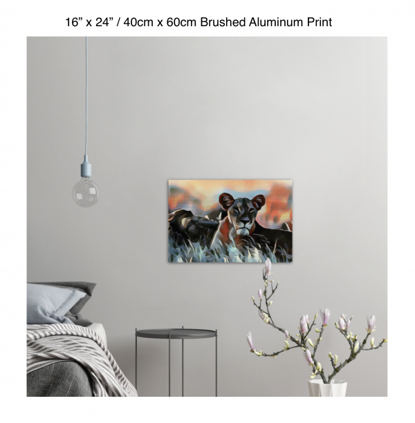 24 inch by 16 inch brushed aluminum print of a lioness hanging in a bedroom over a night table next to a small table with a plant