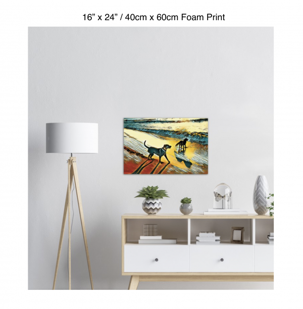 24 inch by 16 inch foam print of two dogs wading in the surf in golden tones of a sunset hanging over a credenza next to a floor lamp