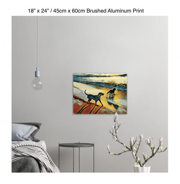 24 inch by 18 inch brushed aluminum print of two dogs wading in the surf in golden tones of a sunset hung on the wall above a metal table next to a bed