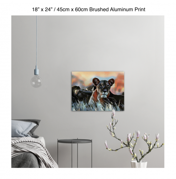 24 inch by 18 inch brushed aluminum print of a lioness hanging in a bedroom over a night table next to a small table with a plant
