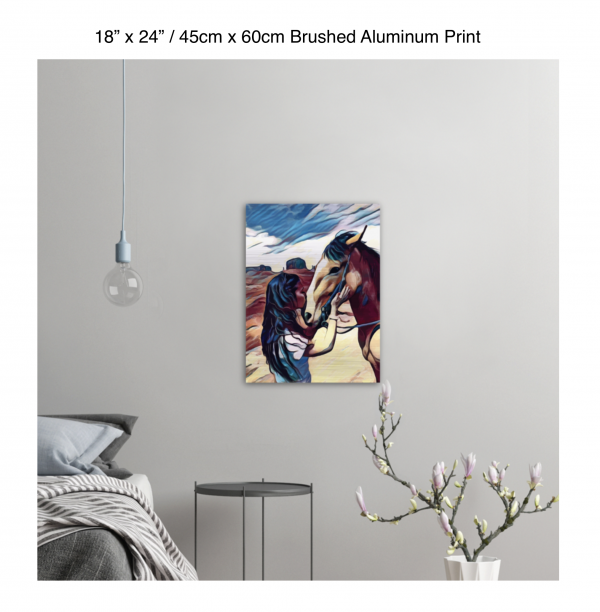 18 inch by 24 inch brushed aluminum print of a woman kissing a horse on the nose in front of a desert background hung on the wall above a metal table next to a bed