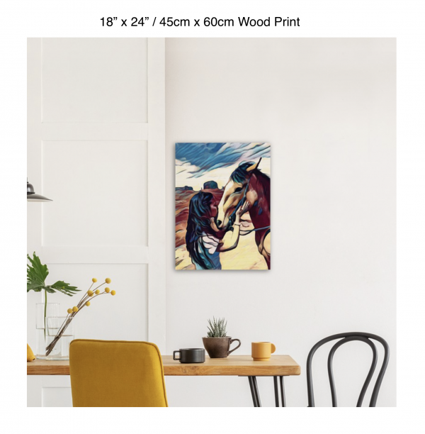 18 inch by 24 inch wood print of a woman kissing the nose of a horse hung above a kitchen table