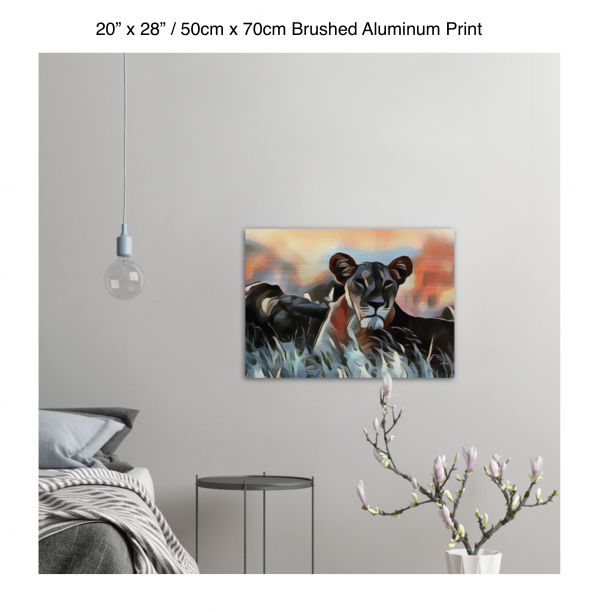 28 inch by 20 inch brushed aluminum print of a lioness hanging in a bedroom over a night table next to a small table with a plant