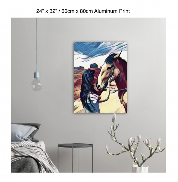 24 inch by 32 inch aluminum print of a woman kissing a horse on the nose in front of a desert background hung on the wall above a metal table next to a bed