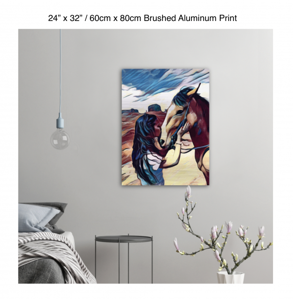 24 inch by 32 inch brushed aluminum print of a woman kissing a horse on the nose in front of a desert background hung on the wall above a metal table next to a bed