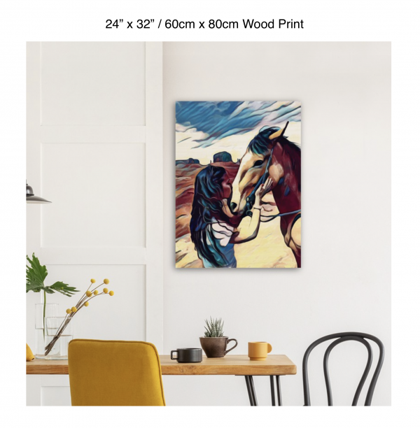24 inch by 32 inch wood print of a woman kissing the nose of a horse hung above a kitchen table