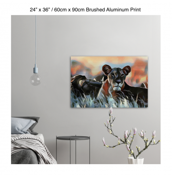 36 inch by 24 inch brushed aluminum print of a lioness hanging in a bedroom over a night table next to a small table with a plant