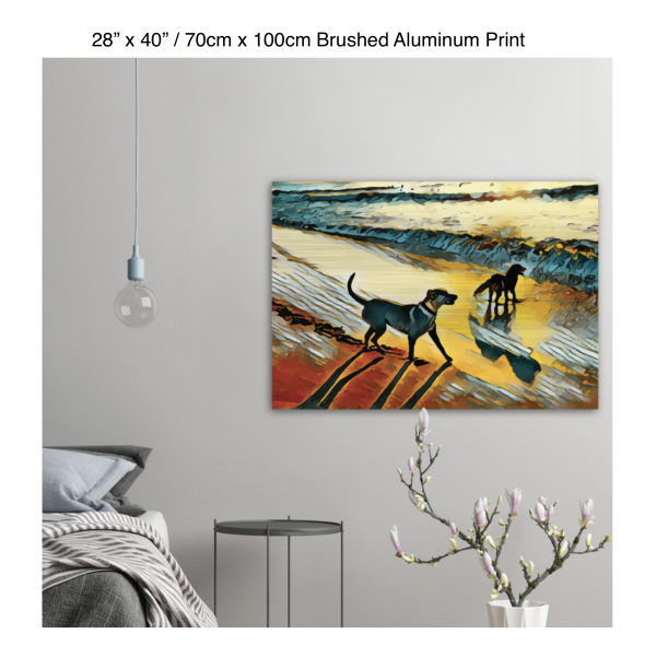 40 inch by 28 inch brushed aluminum print of two dogs wading in the surf in golden tones of a sunset hung on the wall above a metal table next to a bed