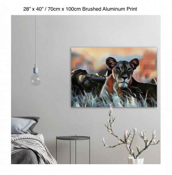 40 inch by 28 inch brushed aluminum print of a lioness hanging in a bedroom over a night table next to a small table with a plant