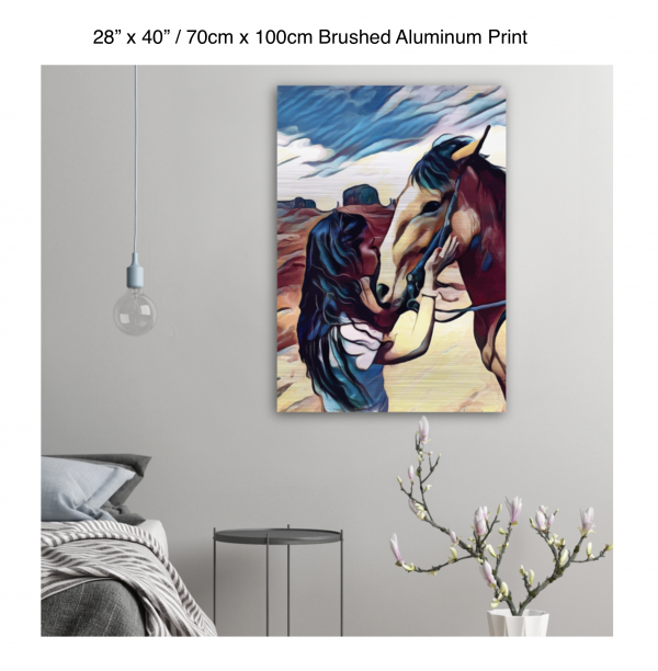 28 inch by 40 inch brushed aluminum print of a woman kissing a horse on the nose in front of a desert background hung on the wall above a metal table next to a bed