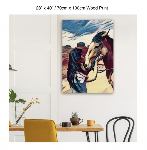 28 inch by 40 inch wood print of a woman kissing the nose of a horse hung above a kitchen table