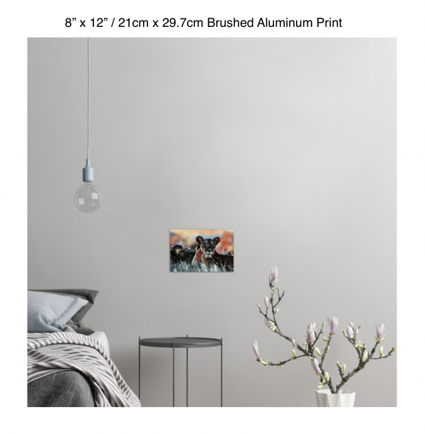12 inch by 8 inch brushed aluminum print of a lioness hanging in a bedroom over a night table next to a small table with a plant