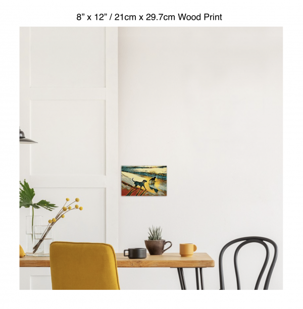 12 inch by 8 inch wood print of two dogs wading in the surf in golden tones of a sunset hung above a kitchen table