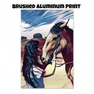 Brushed aluminum print of a woman kissing a horse on the nose in front of a desert background