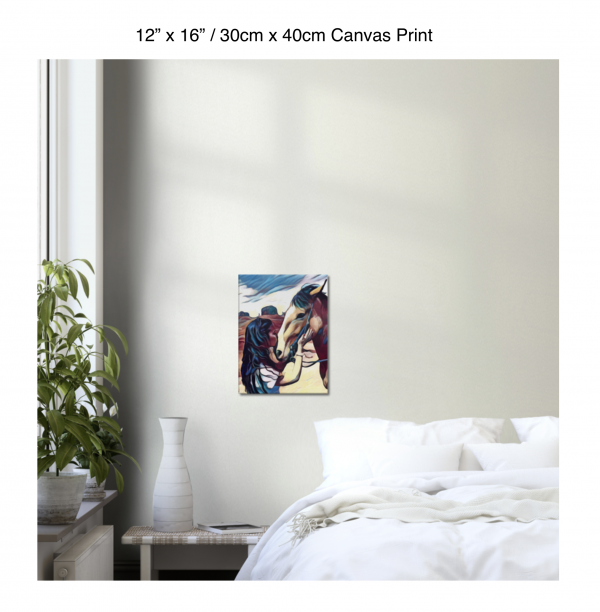 12 inch by 16 inch canvas print of a woman kissing a horse on the nose in front of a desert background hung on the wall above a white bed