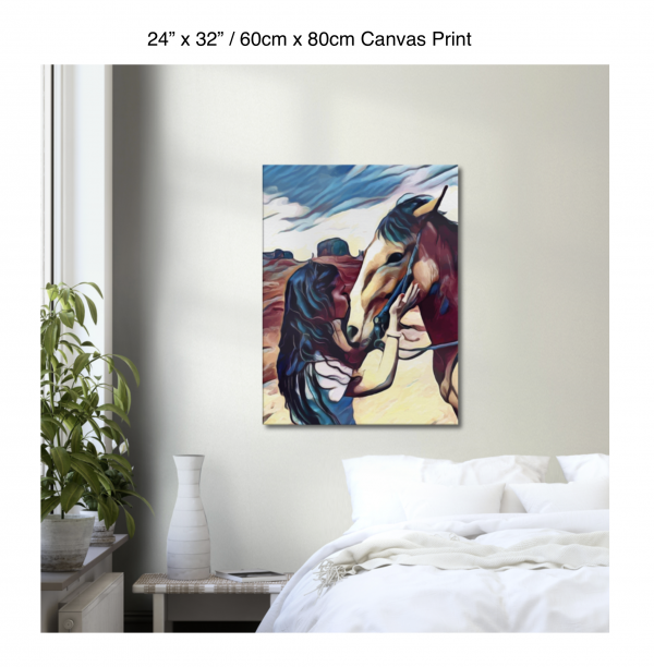 24 inch by 32 inch canvas print of a woman kissing a horse on the nose in front of a desert background hung on the wall above a white bed