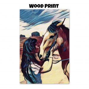 Wood print of a woman kissing a horse on the nose in front of a desert background